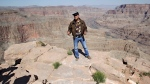 In this May 6, 2011, file photo, Swiss adventurer Yves Rossy, who calls himself the JetMan, stands on the ledge of the Grand Canyon on Guano Point on the Hualapai Indian Reservation to speak to the media. (AP Photo/Matt York, File)