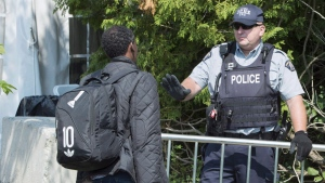 An asylum seeker is questioned by an RCMP officer as he crosses the border into Canada from the United States Monday, August 21, 2017 near Champlain, N.Y. (THE CANADIAN PRESS/Paul Chiasson)