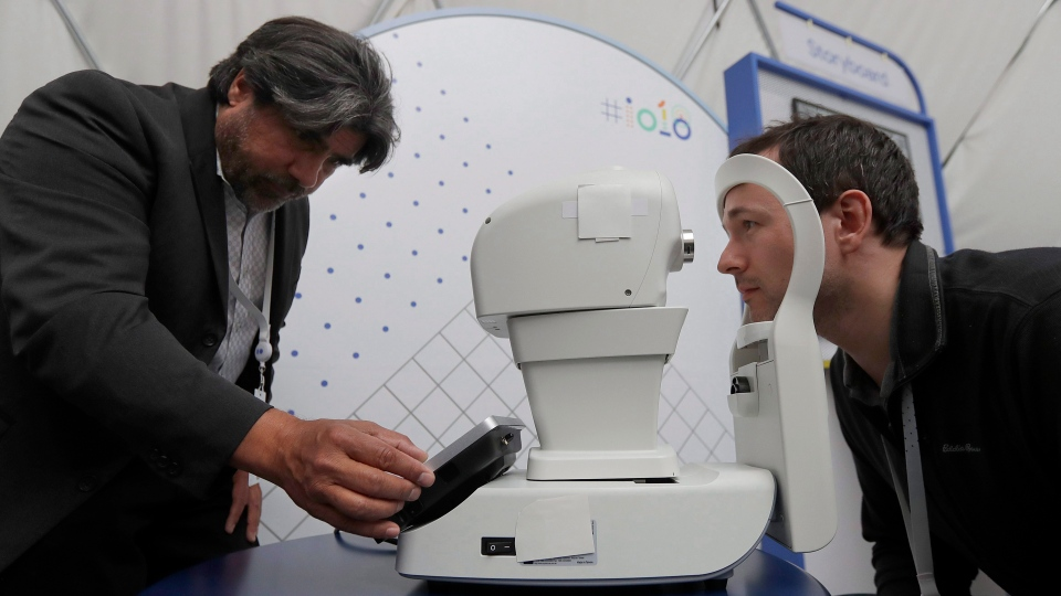 Jorge Cuadros, left, gives a demonstration of a robotic retinal camera to a reporter at the Google I/O conference in Mountain View, Calif., Tuesday, May 8, 2018. (AP Photo/Jeff Chiu)
