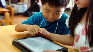 In this July 12, 2018, photo, children work on a digital program at Coby Preschool in Yoshikawa, suburban Tokyo, on an assignment, which was to draw on a triangle on an iPad. For the kids, it's all about having fun. Japanese preschool programs equipped with tablet computers aim to prepare kids for the digital age. (AP Photo/Yuri Kageyama)