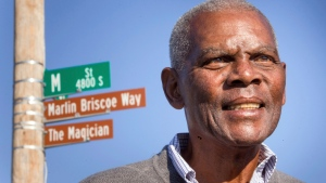 In this Oct. 22, 2014, file photo, Marlin Briscoe stands in front of a street that was renamed for him in Omaha, Neb. The Pro Football Hall of Fame calls the Omaha, Neb. native the first black quarterback in the modern era of pro football. (Kent Sievers/Omaha World-Herald via AP, File)