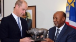 Britain's Prince William, left, is presented with a sculpture of a rhino by Namibia's Vice President Nangolo Mbumba, in Windhoek, Namibia, Monday Sept. 24, 2018. The prince is on a two day visit to the southern African state with the focus being on the illegal wildlife trade. (AP Photo/Dirk Heinrich)