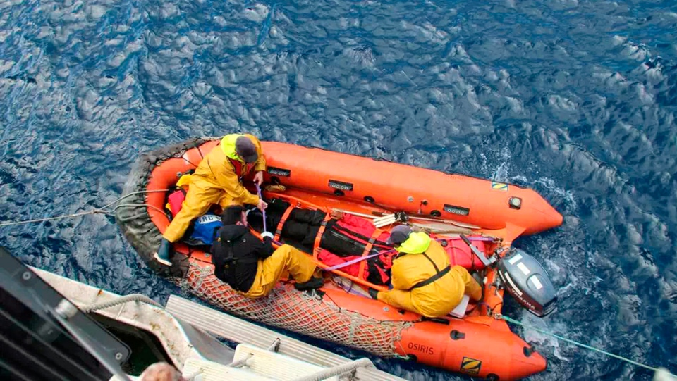 In this photo provided by the Australian Maritime Safety Authority on Tuesday, Sept. 25, 2018, injured Indian sailor Abhilash Tomy lays on the floor of an inflatable boat as rescuers transfer him from his damaged yacht, Thuriya, in the southern Indian Ocean. (AMSA via AP)