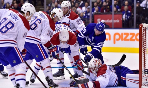 Toronto Maple Leafs centre Par Lindholm (26) looks for a loose puck by Montreal Canadiens goaltender Antti Niemi (37) as Canadiens Nick Suzuki, Brett Lernout, Jacob de la Rose and Karl Alzner (left to right) look on during second period NHL preseason action in Toronto, Monday, Sept. 24, 2018. THE CANADIAN PRESS/Frank Gunn