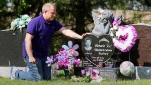 Rodney Stafford, father of slain Victoria (Tori) Stafford puts his hand on Victoria's grave marker, after the sentencing of Michael Rafferty who was found guilty on all three charges at the murder trial in London, Ontario, Tuesday, May 15, 2012. THE CANADIAN PRESS/Dave Chidley