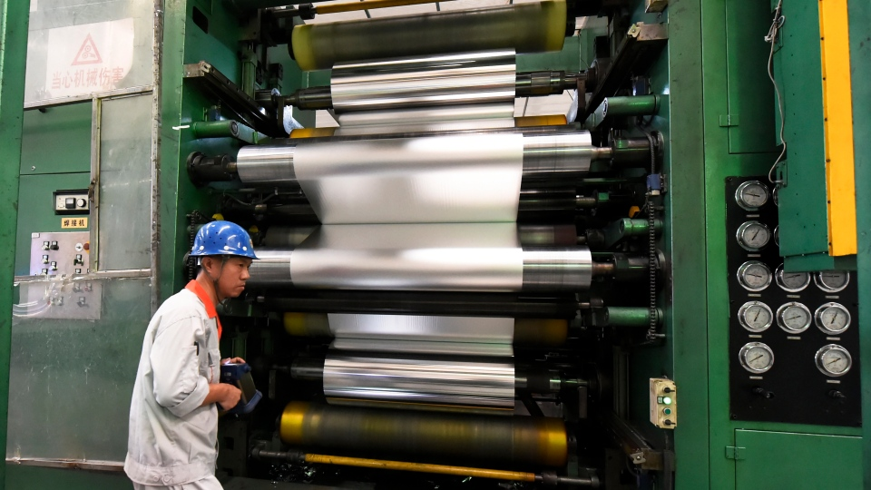 In this Thursday, Sept. 13, 2018, photo, a worker handles a machine roller at an aluminum factory in Zouping in eastern China's Shandong province. China announced more tariff cuts Wednesday, Sept. 26, on construction machinery and other goods but no action on U.S. complaints (Chinatopix via AP)