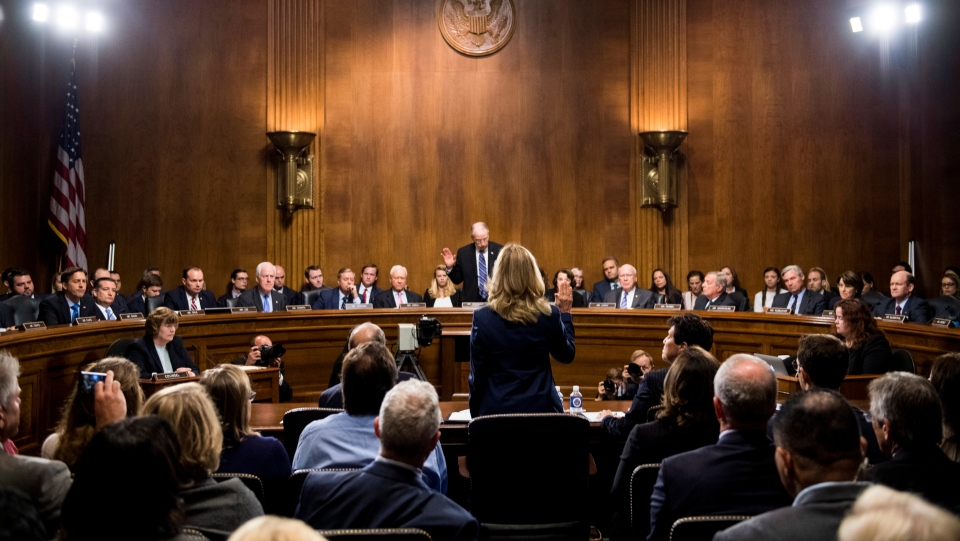 Christine Blasey Ford is sworn in by Senate Judiciary Committee chairman Chuck Grassley, R-Iowa, to testify before the Senate Judiciary Committee on Capitol Hill in Washington, Thursday, Sept. 27, 2018. (Tom Williams/Pool Photo via AP)