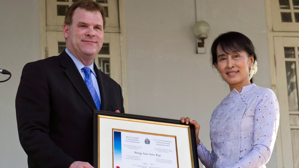 Nobel laureate Aung San Suu Kyi receives her honorary Canadian citizenship from the hands of Foreign Affairs Minister John Baird at her home in Yangon, Myanmar, Thursday, March 8, 2012. (THE CANADIAN PRESS / Paul Chiasson)