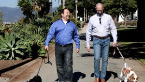 In this Feb. 23, 2012, file photo, Steven May, right, walks with his dog, Winnie beside his attorney, David Pisarra, with his dog, Dudley in Santa Monica, Calif. (AP Photo/Nick Ut, File)
