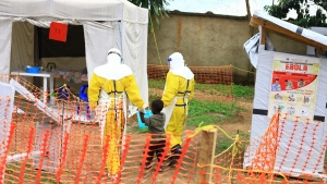 In this Sunday, Sept 9, 2018 file photo, health workers walk with a boy suspected of having the Ebola virus at an Ebola treatment centre in Beni, Eastern Congo. (AP Photo/Al-hadji Kudra Maliro, file)