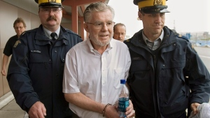 Ernest Fenwick MacIntosh is escorted in custody by RCMP officers at Robert L. Stanfield International Airport in Halifax on Thursday, June 7, 2007. (THE CANADIAN PRESS/Andrew Vaughan)