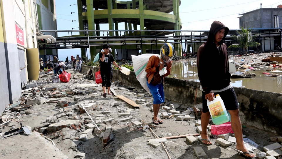 Looters take away items from a shopping mall badly damaged by a massive earthquake and tsunami in Palu, Central Sulawesi, Indonesia, Sunday, Sept. 30, 2018. Rescuers were scrambling Sunday to try to find trapped victims in collapsed buildings where voices could be heard screaming for help after a massive earthquake in Indonesia spawned a deadly tsunami two days ago. (AP Photo/Tatan Syuflana)