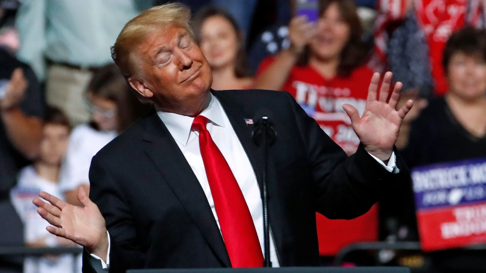 U.S. President Donald Trump reacts to the playing of West Virginia's state song as he takes the stage during a rally in Wheeling, W.Va., Saturday, Sept. 29, 2018. (AP Photo/Gene J. Puskar)
