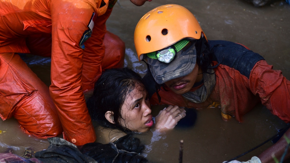 Rescuers try to rescue a 15-year old earthquake victim Nurul Istikharah from her damaged house following earthquakes and tsunami in Palu, Central Sulawesi, Indonesia, Sunday, Sept. 30, 2018. Rescuers were scrambling Sunday to try to find trapped victims in collapsed buildings where voices could be heard screaming for help after a massive earthquake in Indonesia spawned a deadly tsunami two days ago. (AP Photo/Arimacs Wilander)