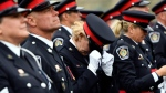 A police officer adjusts her hat before the Canadian Police and Peace Officers Memorial Service on Parliament Hill in Ottawa on Sunday, Sept. 30, 2018. THE CANADIAN PRESS/Justin Tang