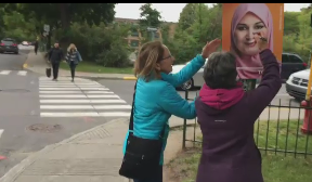 Two women vandalizing a Muslim candidate's poster