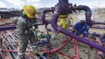 In this March 29, 2013 file photo, workers tend to a well head during a hydraulic fracturing operation at an Encana Oil & Gas (USA) Inc. gas well outside Rifle, in western Colorado. (Brennan Linsley / The Canadian Press / AP)