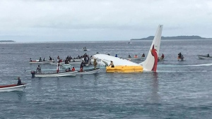 Local fishing boats move in to recover the passengers and crew of Air Niugini flight following the plane crashing into the sea on its approach to Chuuk International Airport in the Federated States of Micronesia., Friday, Sept. 28, 2018. (James Yaingeluo via AP)