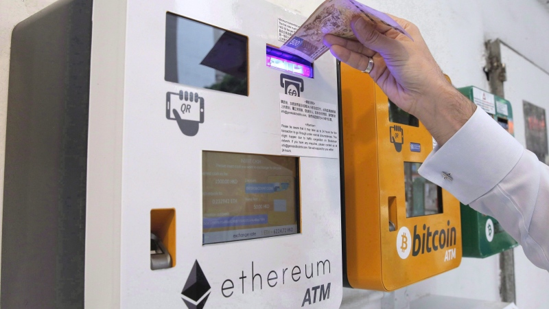 A man uses the Ethereum ATM, beside a Bitcoin ATM, in Hong Kong on May 11, 2018. THE CANADIAN PRESS/AP, Kin Cheung.