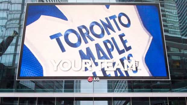 Pedestrians walk past the Air Canada Centre as a screen projects an image of the Toronto Maple Leafs logo in Toronto Wednesday, December 1, 2010. The Toronto Maple Leafs haven't wasted any time filling their executive offices. For the second time in as many days, the Leafs added an assistant general manager on Thursday, hiring Laurence Gilman from the National Hockey League's head office. THE CANADIAN PRESS/Darren Calabrese