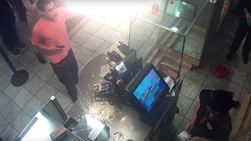 A man dumps an Iced Capp over a Tim Hortons counter in New Westminster, B.C. on Sept. 6, 2018. (Video released by New Westminster police)