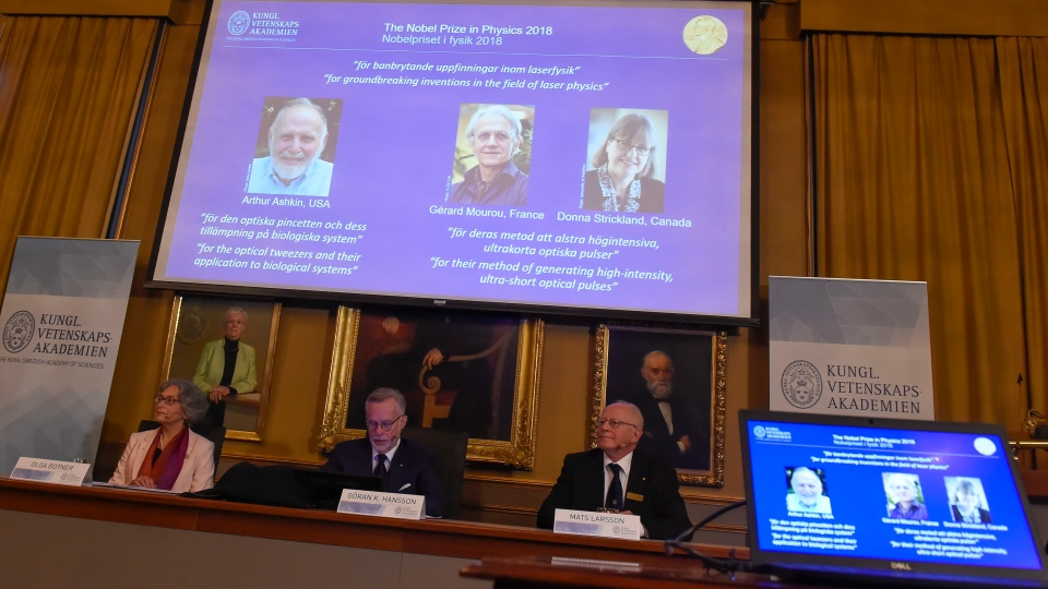 The Nobel Prize laureates for physics 2018 shown on the screen from left, Arthur Ashkin of the United States, Gerard Mourou of France and Donna Strickland of Canada during the announcement at the Royal Swedish Academy of Sciences in Stockholm, Sweden, Tuesday Oct. 2, 2018. (Hanna Franzen/TT via AP)
