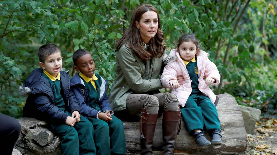 Kate, the Duchess of Cambridge sits on a log with children as she visits the Sayers Croft Forest School and Wildlife Garden at Paddington Recreation Ground, in London, Tuesday Oct. 2, 2018. (Peter Nicholls/Pool Photo via AP)