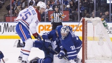 Toronto Maple Leafs goaltender Frederik Andersen makes a stop as Maple Leafs defenceman Ron Hainsey falls into him and Montreal Canadiens' Jacob de la Rose looks on during first period NHL hockey action in Toronto, on April 7, 2018. THE CANADIAN PRESS/Chris Young
