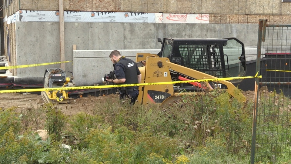 A police officer investigating the scene of a workplace injury in Guelph.