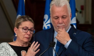 Quebec Premier and Liberal Leader Philippe Couillard pauses as he gets emotional while announcing his resignation as Premier and MNA for the riding of Roberval, Thursday, October 4, 2018 at the legislature in Quebec City. Couillard's wife Suzanne Pilote, left, comforts him. THE CANADIAN PRESS/Jacques Boissinot