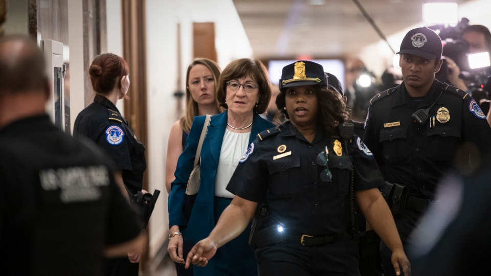 Sen. Susan Collins, R-Maine, is escorted by U.S. Capitol Police past waiting reporters trying to ask about Supreme Court nominee Brett Kavanaugh, on Capitol Hill in Washington, Wednesday, Oct. 3, 2018. (AP Photo/J. Scott Applewhite)