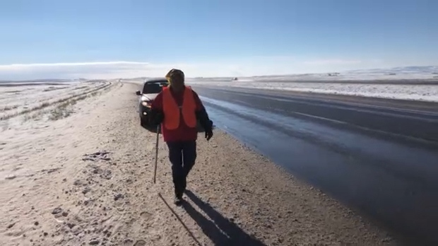 Stephanie English walks along the shoulder of Highway 2, south of Calgary, during her awareness walk for missing and murdered Indigenous women