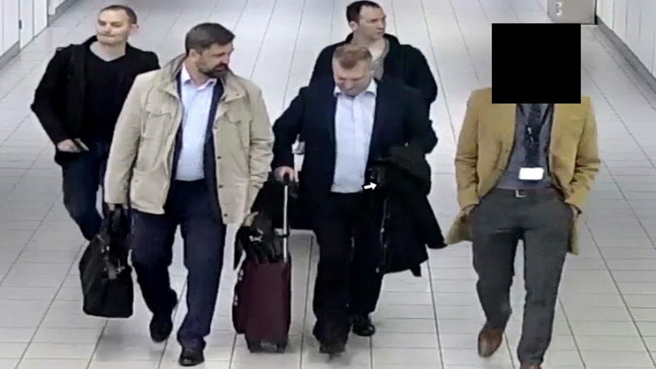 In this image released and manipulated at source by the Dutch Defense Ministry, Thursday Oct. 4, 2018, four Russian officers of the Main Directorate of the General Staff of the Armed Forces of the Russian Federation, GRU, are escorted to their flight after being expelled from the Netherlands on April 13, 2018, for allegedly trying to hack into the U.N. chemical watchdog OPCW's network. (Dutch Defense Ministry via AP)