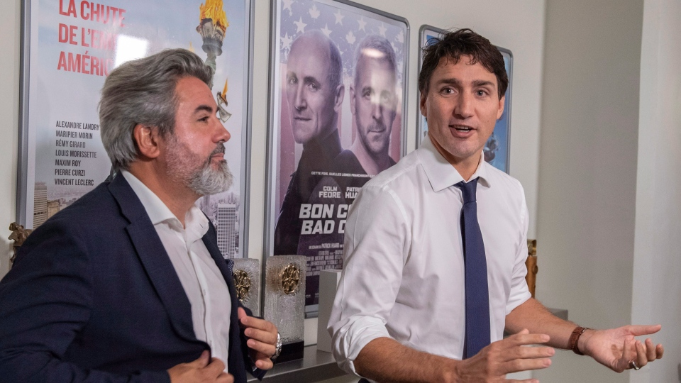 Prime Minister Justin Trudeau stops to answer a few questions as he tours a film production company with Minister of Canadian Heritage and Multiculturalism Pablo Rodriguez in Montreal on Thursday, October 4, 2018. (Paul Chiasson/ The Canadian Press)