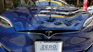 In this Oct. 24, 2016, file photo, palm trees are reflected on the hood of a Tesla Model S on display in downtown Los Angeles. (AP Photo/Richard Vogel)