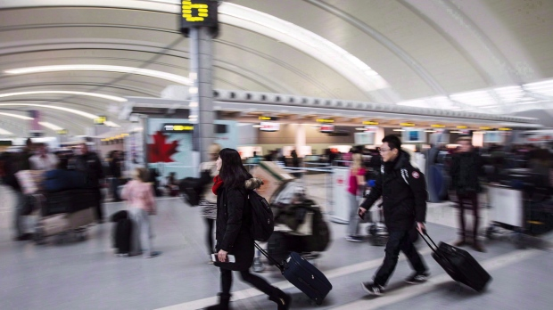People carry luggage at Pearson International Airport in Toronto on December 20, 2013. THE CANADIAN PRESS/Mark Blinch