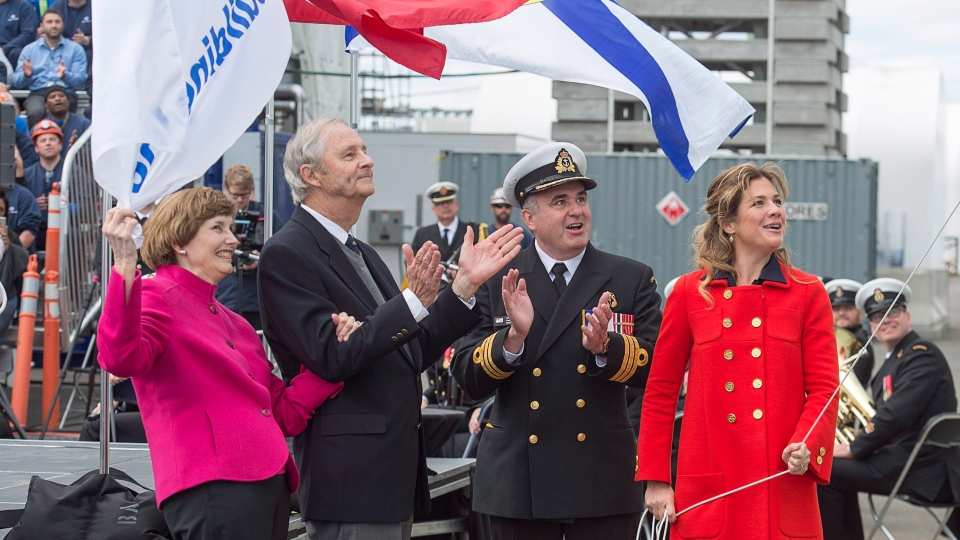 Sophie Gregoire Trudeau (right) releases a bottle of Nova Scotia sparkling wine with James DeWolf, son of the late Harry DeWolf, as his wife Michelle DeWolf, left, and Cmdr. Corey Gleeson look on at the naming ceremony for Canada's lead Arctic and Offshore Patrol Ship, the future HMCS Harry DeWolf, in Halifax on Friday, Oct. 5, 2018. (THE CANADIAN PRESS/Andrew Vaughan)