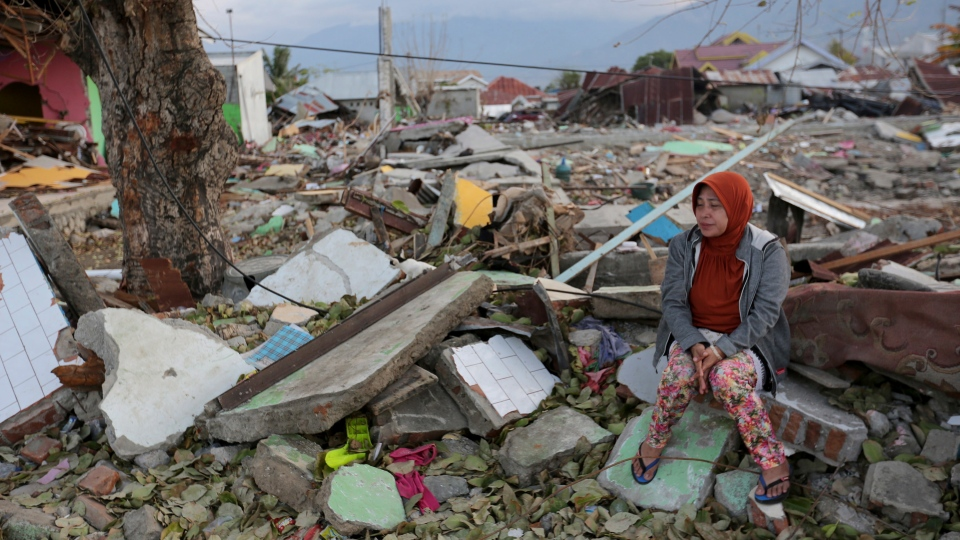A villager sits on the ruins of her house destroyed by an earthquake and tsunami in Palu, Central Sulawesi, Indonesia, Saturday, Oct. 6, 2018. (AP Photo/Tatan Syuflana)