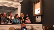 The street artist shared a photo of auction attendees reacting to the artwork self-destructing. (Banksy / Instagram)