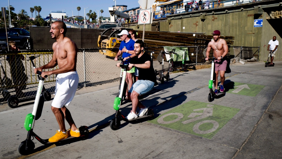 In this July 1, 2018 photo people ride Lime and Bird scooters along the strand in Santa Monica, Calif. (AP Photo/Richard Vogel)