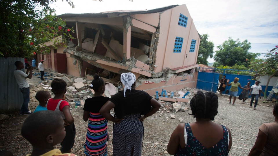 Residents stand looking at a collapsed school damaged bya magnitude 5.9 earthquake the night before, in Gros Morne, Haiti, Sunday, Oct. 7, 2018. (AP Photo/Dieu Nalio Chery)