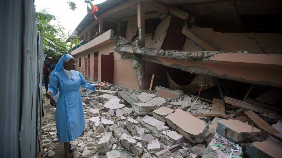 Sr Maryse Alsaint walks alongside a school damaged by a magnitude 5.9 earthquake the night before, in Gros Morne, Haiti, Sunday, Oct. 7, 2018. (AP Photo/Dieu Nalio Chery)