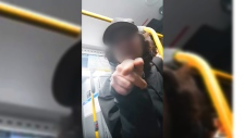 A man on a bus acts aggressively towards woman