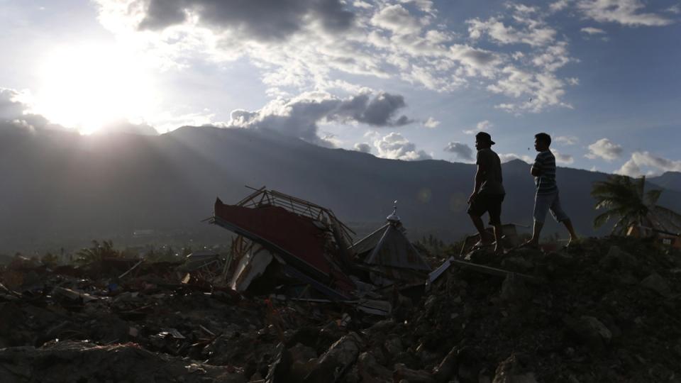 Indonesian men survey the damage at the devastated village of Balaroa as the sun sets in Palu, Central Sulawesi, Indonesia, on Oct. 8, 2018. (Dita Alangkara / AP)