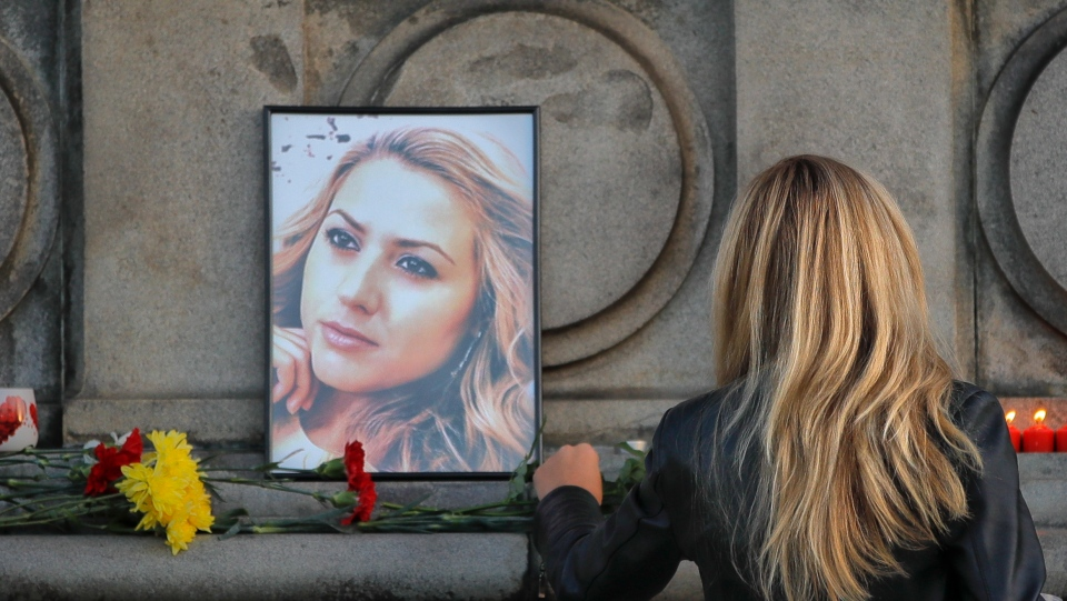 A woman places flowers next to a portrait of slain television reporter Viktoria Marinova during a vigil at the Liberty Monument in Ruse, Bulgaria, Monday, Oct. 8, 2018.  (AP Photo/Vadim Ghirda)