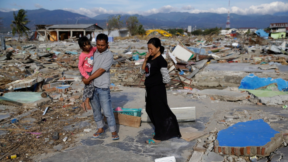 In this Oct. 5, 2018, photo, Musrifah, right, holds back tears beside her husband Hakim and daughter Syafa Ramadi as they visit where their house once stood before a massive earthquake and tsunami hit their seaside village in Palu, Central Sulawesi, Indonesia. The family lost their son. (AP Photo/Aaron Favila)