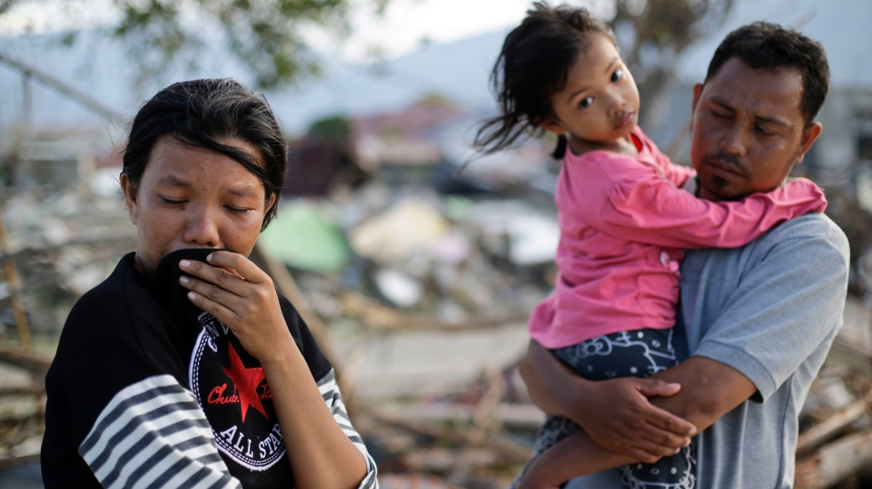 In this Oct. 5, 2018, photo, Musrifah, left, cries beside her husband Hakim and daughter Syafa Ramadi as they visit the area where their house used to stand before a massive earthquake and tsunami hit their seaside village in Palu, Central Sulawesi, Indonesia. (AP Photo/Aaron Favila)
