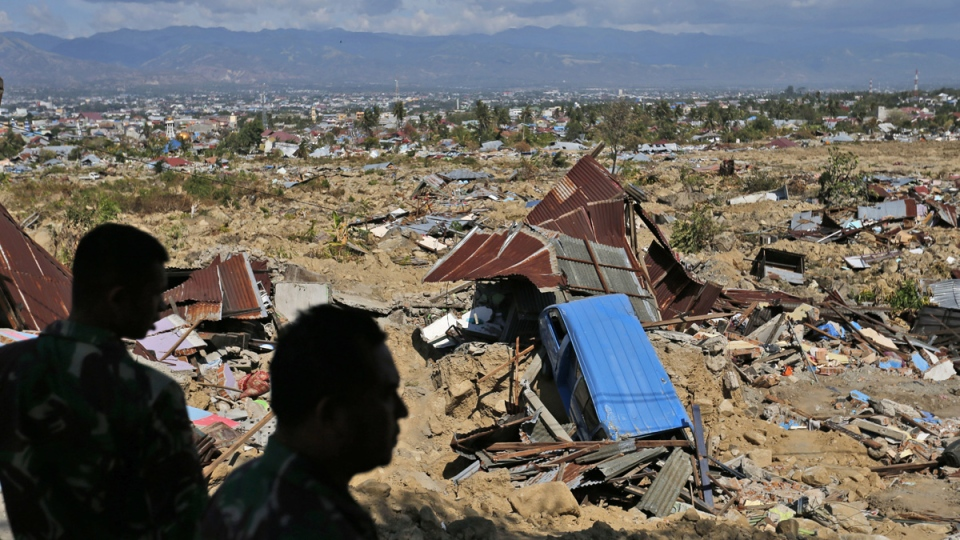 Soldiers survey the damage in a Balaroa neighbourhood wiped out by earthquake-triggered liquefaction in Palu, Central Sulawesi, Indonesia. (Dita Alangkara / AP)