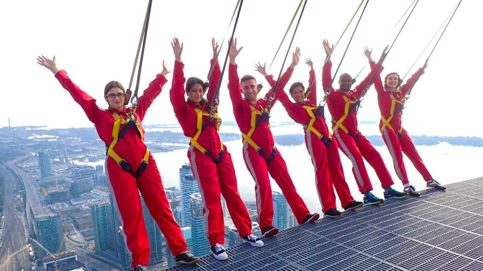 This photo taken from Immigration, Refugees and Citizenship Canada (IRCC) shows six new Canadians taking their oaths of citizenship on the CN Tower EdgeWalk, in Toronto, on Tuesday, Oct. 9, 2018. (IRCC / Twitter)