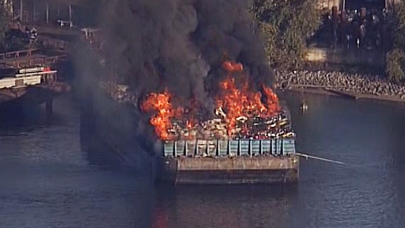Flames pour from a barge fire near Surrey, B.C. on Tuesday, Oct. 9, 2018.